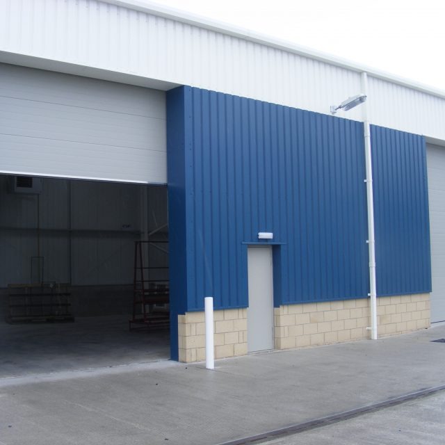 Grey roller shutters for a blue warehouse