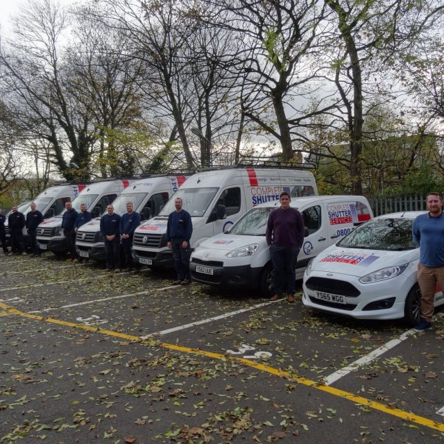 Complete Shutter Services Group Photo with Company Vans