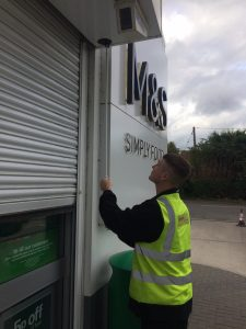 Engineer checking roller shutter operation at an M&S Food store